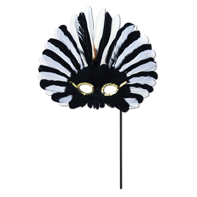 Black and white feathered mask with gold accents around the eyes attached to a black stick.