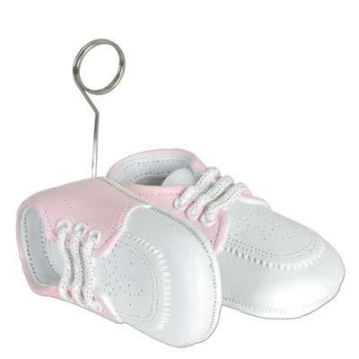 Balloon weights of pink baby shoes with metal balloon holder.